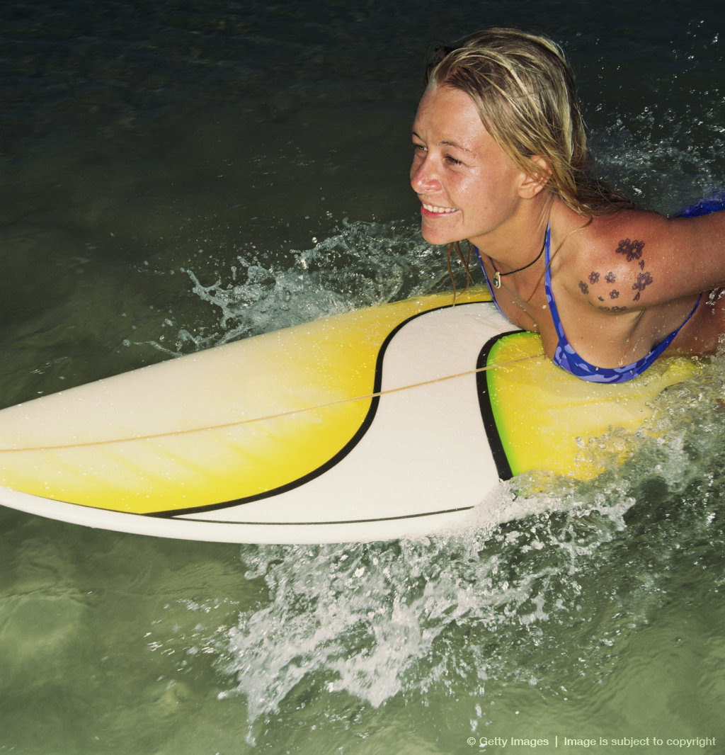 Female surfer lying on board, elevated view