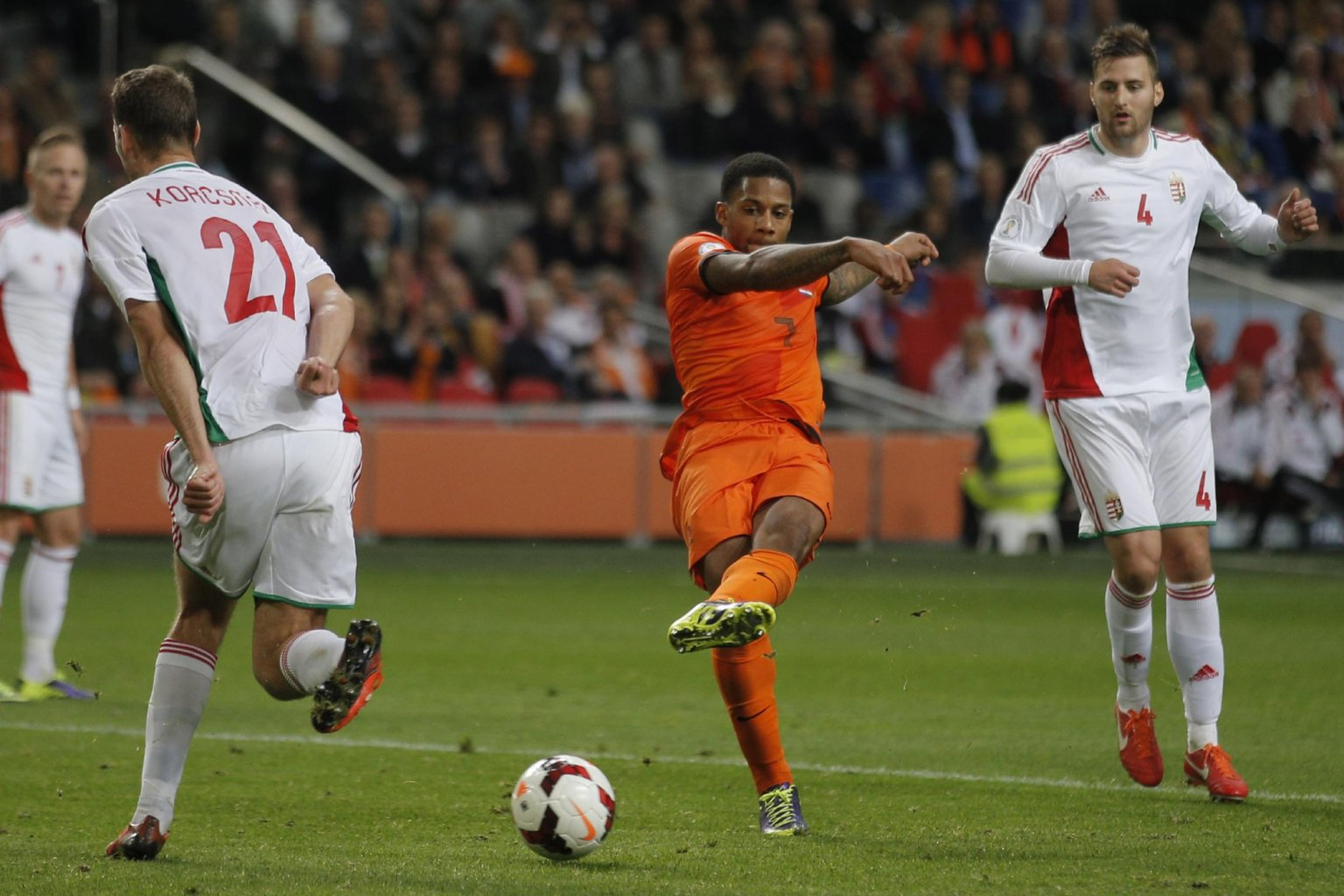 Netherlands' Jeremain Lens, center, scores 3-0 passing Hungary's Zsolt Korcsmar, left, and Hungary's Tamas Kadar, right, during the Group D World Cup qualifying...
