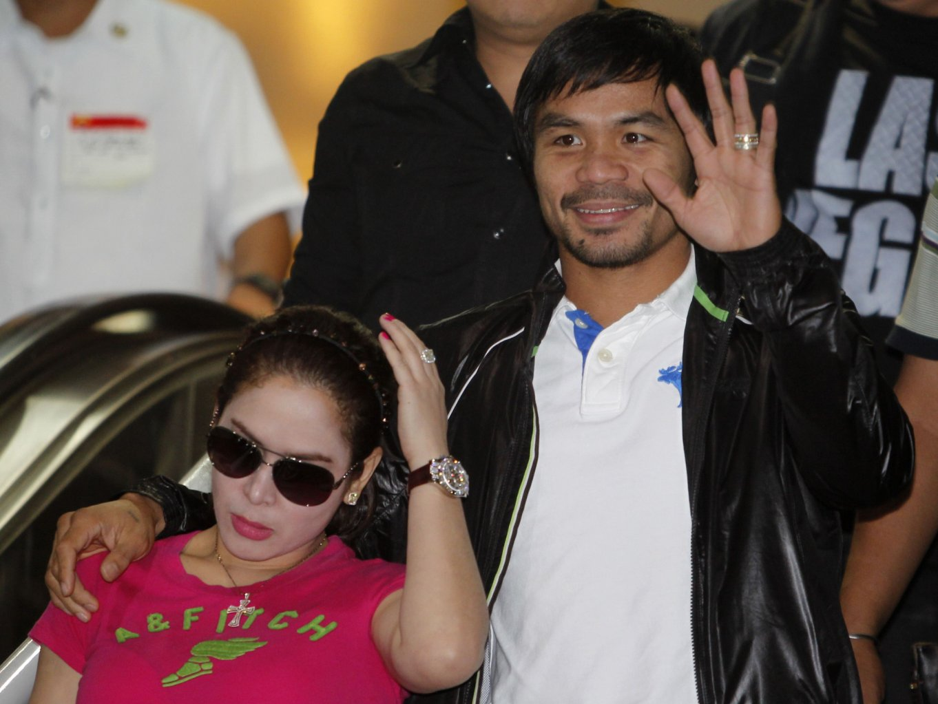 Filipino boxing icon Manny Pacquiao waves beside his wife Jinkee upon his arrival at the Ninoy Aquino International Airport in Manila