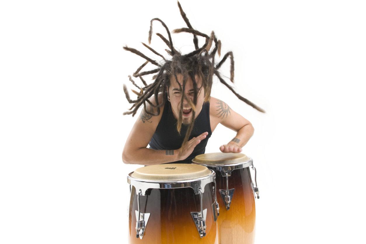 Man with dreadlocks playing bongo drum, studio shot